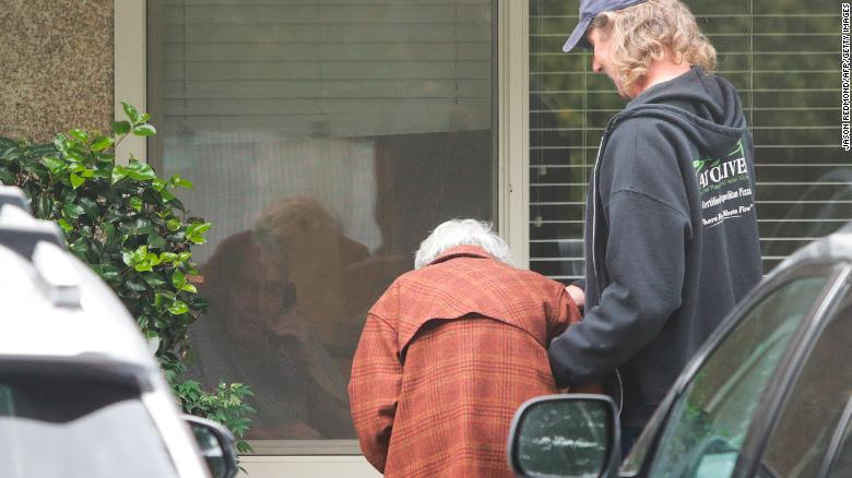 Charlie Campbell  takes his mom Dorothy Campbell, 88, to see her husband Gene Campbell, 89, through his room window at the Life Care Center nursing home in Kirkland, Washington.