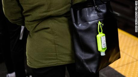 A hand sanitizer dispenser hangs from a subway rider's bag at the Times Square station in Manhattan.