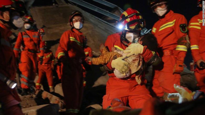 Rescuers carried a young boy from the rubble.