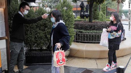 A staff member checks the body temperature of visitors outside Disneytown in Shanghai on Monday.