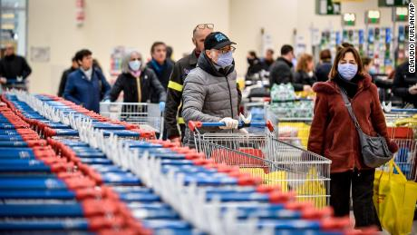 People wear masks while shopping at a supermarket in Milan, after Italy announced a sweeping quarantine zone covering its northern regions.