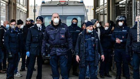 Prison officers stand guard as an ambulance enters SantAnna prison in Modena, inside one of Italy's quarantine red zones, following a disturbance there.