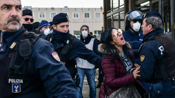 """Police officers restrain the relative of an inmate outside the Sant'Anna jail in Modena, Italy, on March 9. <a href=""""https://www.cnn.com/asia/live-news/coronavirus-outbreak-03-09-20-intl-hnk/h_950c62671e245816c223fb84f1306fe6"""" target=""""_blank"""">Riots broke out</a> in several Italian jails after visits were suspended to curb the spread of the coronavirus."""