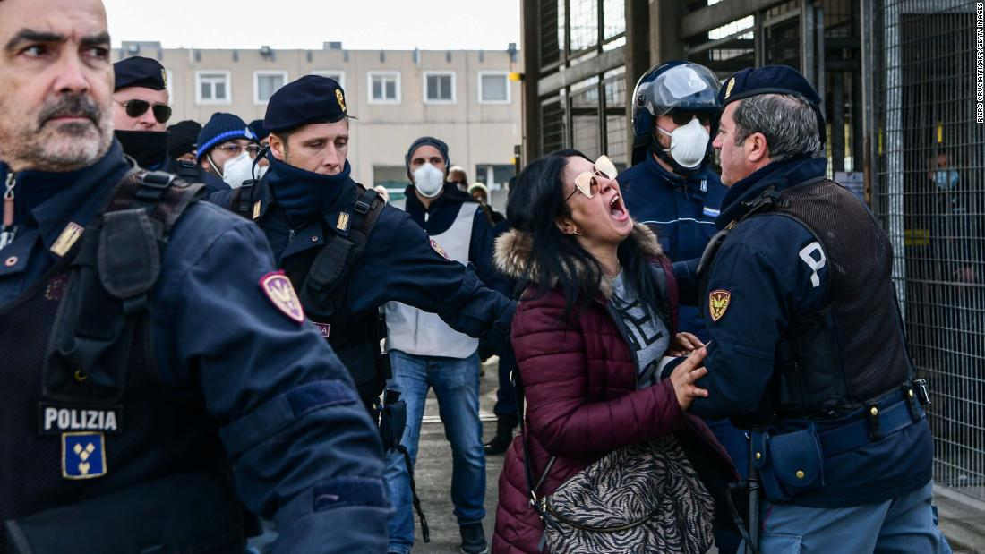"Police officers restrain the relative of an inmate outside the Sant'Anna jail in Modena, Italy, on March 9. <a href=""https://www.cnn.com/asia/live-news/coronavirus-outbreak-03-09-20-intl-hnk/h_950c62671e245816c223fb84f1306fe6"" target=""_blank"">Riots broke out</a> in several Italian jails after visits were suspended to curb the spread of the coronavirus."