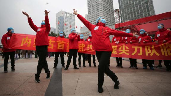 Medical staff in Wuhan, China, celebrate after all coronavirus patients were discharged from a temporary hospital on March 9.