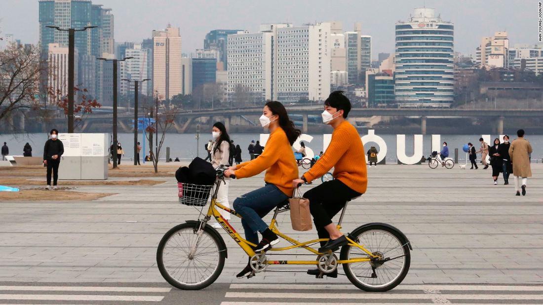 A couple rides a bicycle at a park in Seoul, South Korea, on March 7.