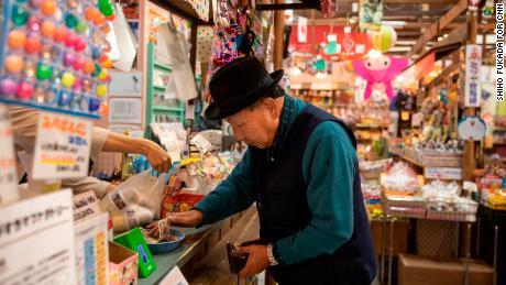 Iwao Hakamada buys himself an ice cream as he takes his daily walk around Hamamatsu,