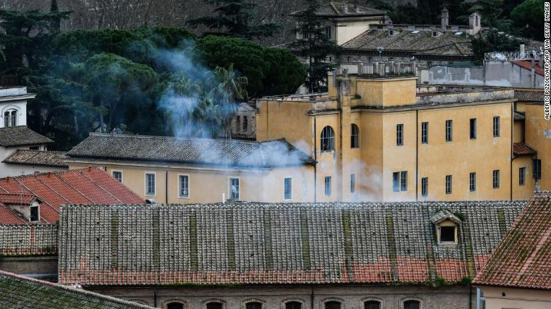 Smoke billows from a rooftop of the Regina Coeli prison in central Rome on Monday.