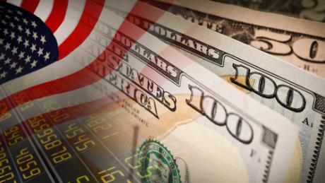 American flag and banknotes (USD) currency money on Stock market background.