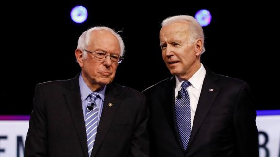 Sanders and former Vice President Joe Biden talk before a Democratic debate in Charleston, South Carolina, in February 2020.