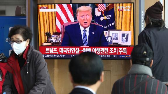"""People at a railway station in Seoul, South Korea, watch a live broadcast of US President Donald Trump on March 12. Trump announced that, in an effort to slow the spread of the coronavirus, he would <a href=""""https://www.cnn.com/2020/03/11/politics/donald-trump-coronavirus-statement/index.html"""" target=""""_blank"""">sharply restrict travel</a> from more than two dozen European countries."""