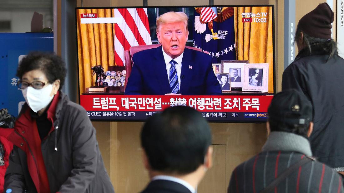 "People at a railway station in Seoul, South Korea, watch a live broadcast of US President Donald Trump on March 12. Trump announced that, in an effort to slow the spread of the coronavirus, he would <a href=""https://www.cnn.com/2020/03/11/politics/donald-trump-coronavirus-statement/index.html"" target=""_blank"">sharply restrict travel</a> from more than two dozen European countries."