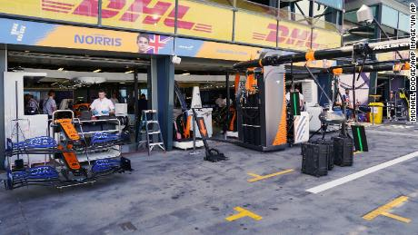 Technicians work around equipment and car parts in the The McLaren team pit at the Australian Formula One Grand Prix.