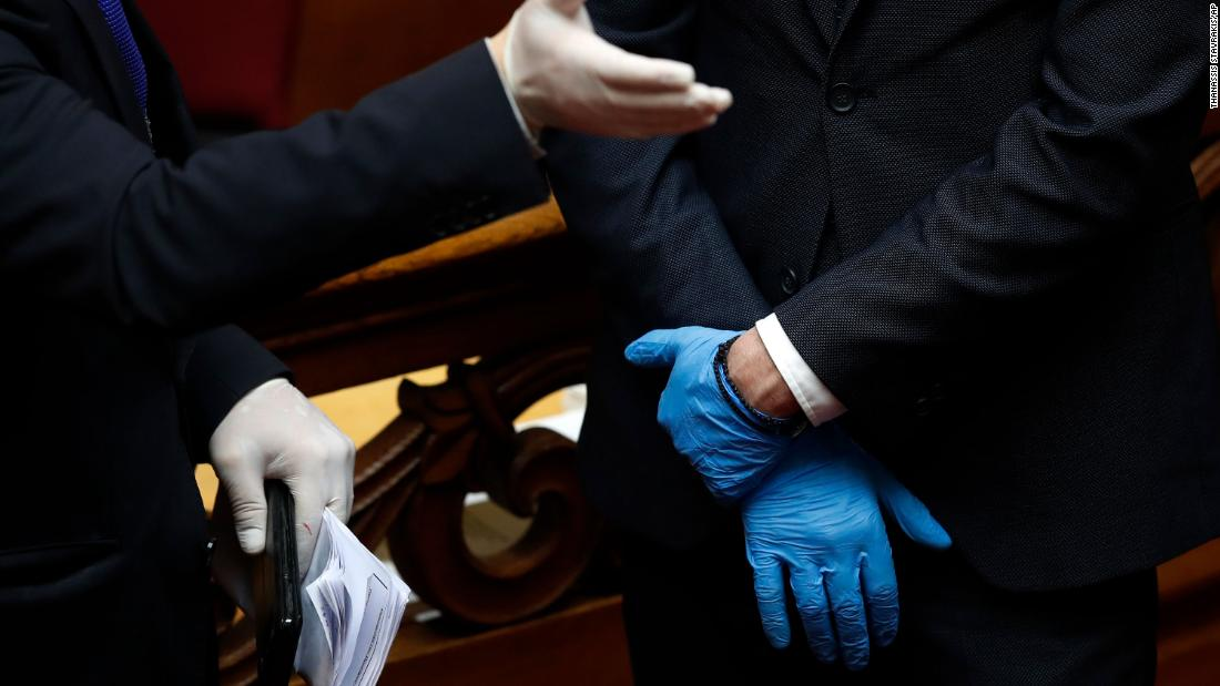 Employees of the Greek Parliament wear plastic gloves ahead of the swearing-in ceremony for Greek President Katerina Sakellaropoulou.