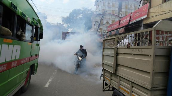 A motorcyclist drives through disinfectant sprayed in Jammu, India, on March 13.