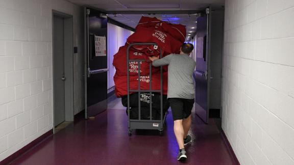 Paul Boyer, head equipment manager of the NHL's Detroit Red Wings, wheels out equipment bags in Washington on Thursday, March 12. The NHL is among the sports leagues that have suspended their seasons.