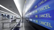 A flight arrival information board displays cancelled flights at an airport in Japan.