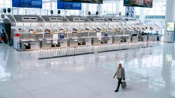 """A man walks past the closed Air France counters at the Terminal 1 section at John F. Kennedy International Airport on March 12, 2020 in New York City. - US President Donald Trump announced a shock 30-day ban on travel from mainland Europe over the coronavirus pandemic that has sparked unprecedented lockdowns, widespread panic and another financial market meltdown Thursday.The announcement came as China, where the outbreak that first emerged in December, showed a dramatic drop in new cases and claimed """"the peak"""" of the epidemic had passed. (Photo by Kena Betancur / AFP) (Photo by KENA BETANCUR/AFP via Getty Images)"""