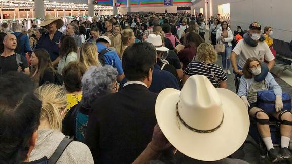 """People wait in line to go through customs at Dallas/Fort Worth International Airport on March 14. Travelers returning from Europe say they were <a href=""""https://www.cnn.com/travel/article/coronavirus-airport-screening-sunday/index.html"""" target=""""_blank"""">being made to wait for hours </a>at US airports, often in close quarters, as personnel screened them for the coronavirus."""