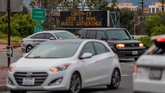 """A Caltrans Changeable Message Sign (CMS) warns motorists along California State Route 135 to avoid gatherings as the threat of Coronavirus disease (COVID-19) increases throughout the nation, in Glendale, California, on March 14, 2020. - The World Health Organization said March 13, 2020 it was not yet possible to say when the COVID-19 pandemic, which has killed more than 5,000 people worldwide, will peak. """"It's impossible for us to say when this will peak globally,"""" Maria Van Kerkhove, who heads the WHO's emerging diseases unit, told a virtual press conference, adding that """"we hope that it is sooner rather than later"""". (Photo by DAVID MCNEW / AFP) (Photo by DAVID MCNEW/AFP via Getty Images)"""
