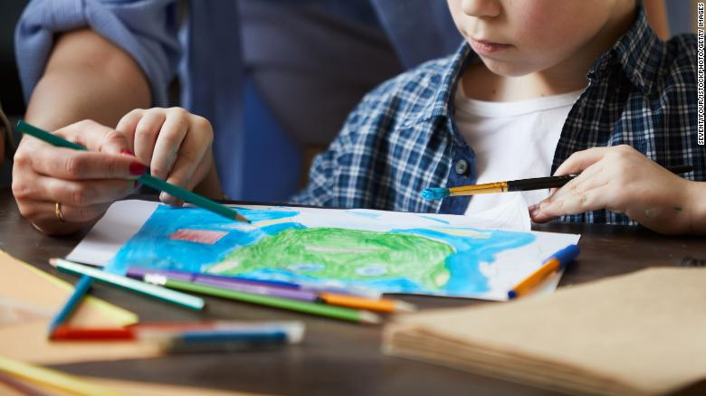 Portrait of cute little boy painting picture with mom helping him, copy space