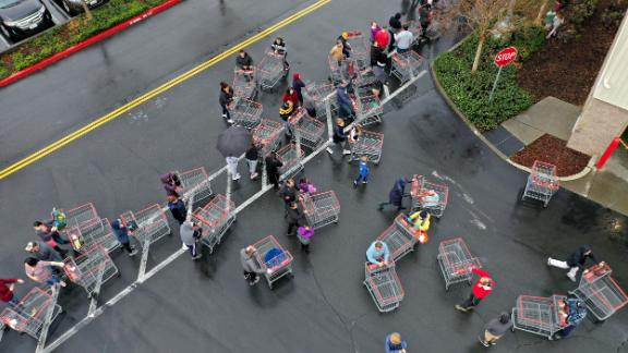 """Hundreds of people lined up to enter a Costco in Novato, California, on March 14. Many people have been stocking up on food, toilet paper and other items. As a response to <a href=""""https://www.cnn.com/2020/03/09/health/toilet-paper-shortages-novel-coronavirus-trnd/index.html"""" target=""""_blank"""">panic buying,</a> retailers in the United States and Canada have started limiting the number of toilet paper that customers can buy in one trip."""