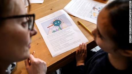 A mother helps her 5-year-old child to do school homeworks on the COVID-19 coronavirus on March 12, 2020 in Manta, near Cuneo, Northwestern Italy, as Italy shut all stores except for pharmacies and food shops in a desperate bid to halt the spread of a coronavirus that has killed 827 in the the country in just over two weeks.