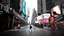A tourist crosses the 7th Avenue at Times Square on March 13, 2020 in New York City. (Photo by Johannes Eisele/AFP/Getty Images)