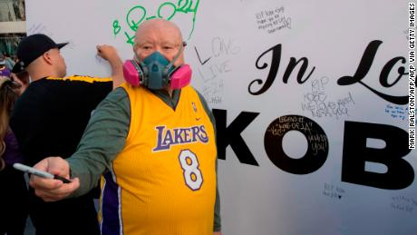A Lakers fan wears a mask to protect against the Coronavirus as he pays his respects at a Staples Center memorial wall to NBA legend Kobe Bryant,