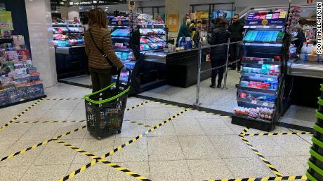 At a supermarket in central Madrid, lines taped on the ground indicate how far apart customers should stand.
