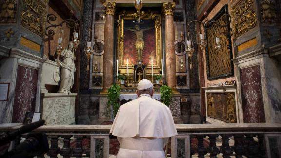 """Pope Francis, inside the Church of San Marcello in Rome's city center,<a href=""""https://edition.cnn.com/2020/03/16/europe/pope-francis-prayer-coronavirus-plague-crucifix-intl/index.html"""" target=""""_blank""""> prays at a famous crucifix</a> that believers claim helped to save Romans from the plague in 1522."""