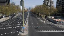 A woman crosses the usually busy La Castellana avenue in Madrid on March 15, 2020.