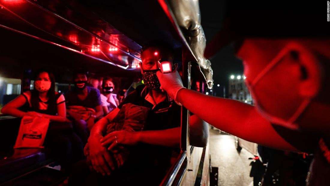 A police officer checks the temperatures of bus passengers at a checkpoint in Manila, Philippines, on March 16.