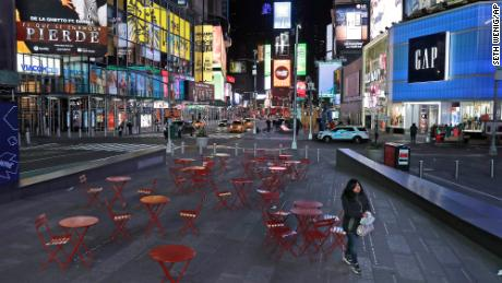 A woman walks through a lightly trafficked Times Square in New York on March 16.