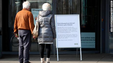 A couple stands in front of a sign that says a store is closed in Germany.