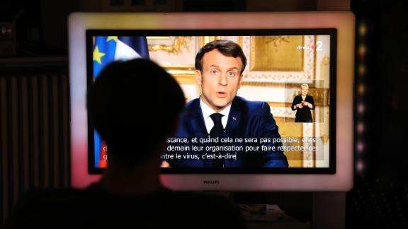 """French President Emmanuel Macron is seen on a screen in Paris as he announces new coronavirus containment measures on March 16. <a href=""""https://www.cnn.com/world/live-news/coronavirus-outbreak-03-17-20-intl-hnk/h_da63d65d14fcffbc7105f1a287478a55"""" target=""""_blank"""">France has been put on lockdown,</a> and all nonessential outings are outlawed and can draw a fine of up to €135 ($148). Macron also promised to support French businesses by guaranteeing €300 billion worth of loans and suspending rent and utility bills owed by small companies."""