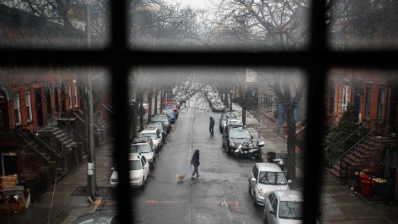 A pedestrian walks a dog through a quiet street in New York on March 17.