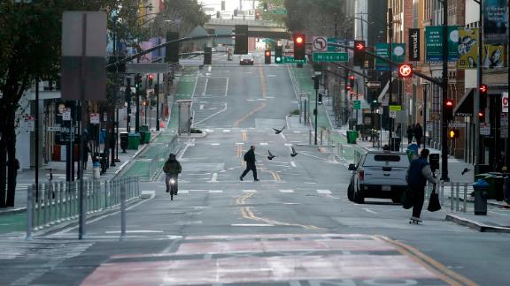 A man crosses a nearly empty street in San Francisco, Tuesday, March 17, 2020. Officials in seven San Francisco Bay Area counties have issued a shelter-in-place mandate affecting about 7 million people, including the city of San Francisco itself. The order says residents must stay inside and venture out only for necessities for three weeks starting Tuesday. (AP Photo/Jeff Chiu)