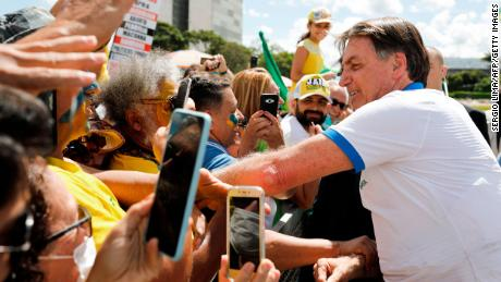 Brazilian President Jair Bolsonaro greets supporters in front of the Planalto Palace on March 15.