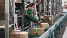 A worker packs goods at a logistics center in Beijing, capital of China, March 12, 2020.