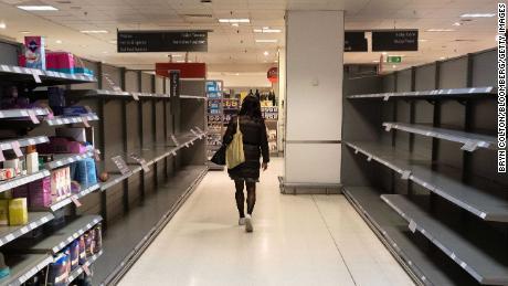 A customer walks past empty shelves in a Waitrose supermarket in London.