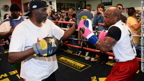 Floyd Mayweather Jr. (R) works out with his trainer and uncle Roger Mayweather at the Mayweather Boxing Club in 2014.