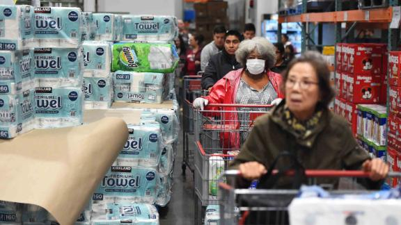 A line of shoppers wait to collect toilet paper at a Costco store in Novato, California on March 14, 2020. - Hoards of shoppers rushed to stock up on toilet paper, paper towels and cleaning supplies as communities begin hunkering down as a result of the Coronavirus. (Photo by Josh Edelson / AFP) (Photo by JOSH EDELSON/AFP via Getty Images)