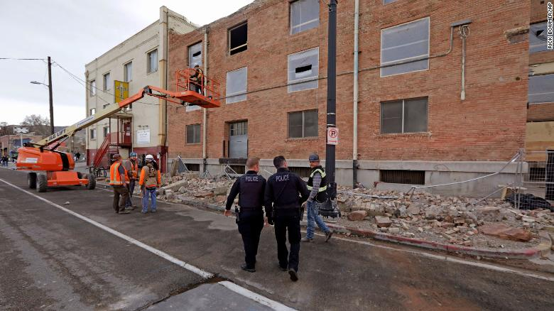 Police officers walk past rubble in Salt Lake City after Wednesday's earthquake.