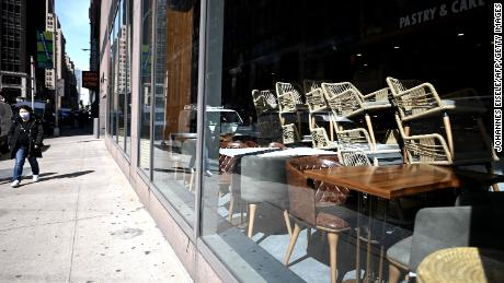 Chairs are stacked in a closed Cafe in Manhattan on March 16, 2020 in New York City. - Stocks tumbled on March 16, 2020 despite emergency central bank measures to prop up the virus-battered global economy, as countries across Europe started the week in lockdown and major US cities shut bars and restaurants. The virus has upended society around the planet, with governments imposing restrictions rarely seen outside wartime, including the closing of borders, home quarantine orders and the scrapping of public events including major sporting fixtures. (Photo by Johannes Eisele/AFP/Getty Images)
