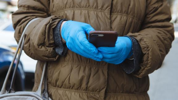A person wears protective gloves while using a mobile phone in New Rochelle, New York, U.S., on Monday, March 16, 2020. The governors of New York, New Jersey and Connecticut banned all gatherings of 50 or more people, and said bars, restaurants, casinos and gyms must close Monday at 8 p.m. Photographer: Angus Mordant/Bloomberg via Getty Images
