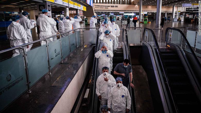 3月18日,星期三,身穿防护服的医务人员在莫斯科谢列梅捷沃国际机场乘坐自动扶梯顺行。