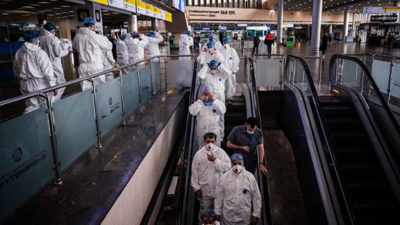 Medical staff wearing protective suits ride down an escalator at Moscow's Sheremetyevo International Airport on Wednesday, March 18.