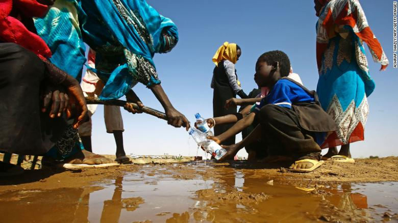 A Sudanese woman fills water bottles held by a young boy near the capital of the North Darfur State.