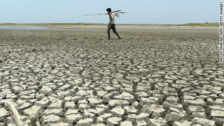 A man walks over the parched bed of a reservoir on the outskirts of Chennai, India.